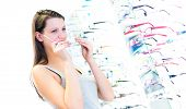 Pretty, young woman choosing new glasses frames in an optician store (color toned image; shallow DOF