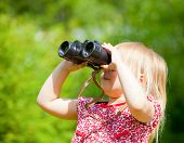 Little girl looking through binoculars outdoor
