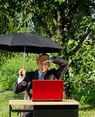 Freelance concept. Businessman working outdoors, hiding from the sun under umbrella