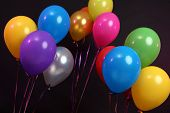 image of helium  - Many bright balloons isolated on black - JPG