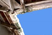 image of derelict  - upward view of mouldy neglected asbestos guttering - JPG