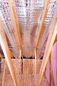 foto of attic  - Continuous work of insulating of attic with reflective heat barrier between the attic joists and knee wall