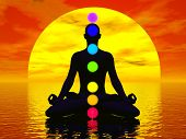 stock photo of kundalini  - Silhouette of a man meditating with seven colorful chakras upon ocean by red sunset - JPG