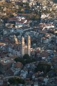 picture of taxco  - SANTA PRISCA CATHEDRAL IN TAXCO MEXICO WITH SUNLIGHT STRIKING BELL TOWERS AGAINST CITY BACKGROUND - JPG