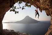 stock photo of cave  - Rock climber at sunset - JPG