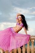 stock photo of bannister  - A beautiful belly dancer wearing a dusty rose colored costume poses on a stone balustrade - JPG