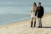 foto of suny  - Young couple walking on the beach in suny day - JPG