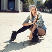 foto of skate board  - Young trendy girl in sunglasses and a knitted hat sitting on a skateboard on the background of a large street - JPG
