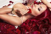stock photo of red lingerie  - sexy woman with long red hair in lingerie lying on rose - JPG