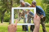 pic of extended family  - Hand holding tablet pc showing extended family having fun in the park - JPG