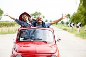 stock photo of leaving  - Happy senior couple driving vintage car - JPG