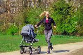 stock photo of buggy  - Smiling young woman pushing baby buggy while exercising in a park - JPG