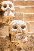 pic of cultural artifacts  - Closeup of scary Mexican stone skulls with stairs in the background - JPG