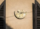 pic of sundial  - sundial on a house wall in the morning sun - JPG