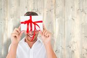 stock photo of pale  - Man holding gift against pale wooden planks - JPG