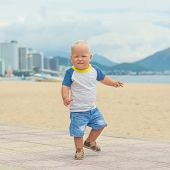 stock photo of laughable  - Baby walking along the beach - JPG