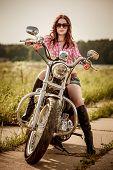foto of biker  - Biker girl with sunglasses sitting on motorcycle - JPG