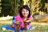 stock photo of food chain  - Woman lying on the grass with food - JPG