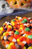 picture of cobweb  - a pile of different Halloween candies with scary ornaments in the background - JPG