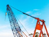 stock photo of lift truck  - The grunge construction crane for heavy lifting is working in construction site and clear blue sky day - JPG