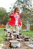 picture of sensory perception  - Five year old girl walking over pebbles - JPG