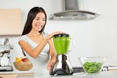 image of carrot  - Vegetable smoothie woman blending green smoothies with blender home in kitchen - JPG