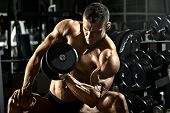 stock photo of darkness  - very power athletic guy bodybuilder execute exercise with dumbbells in dark gym - JPG