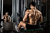 stock photo of execution  - very power athletic guy bodybuilder execute exercise with gym apparatus on broadest muscle of back - JPG