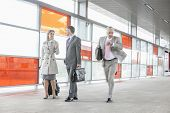 picture of late 20s  - Businesspeople walking while male colleague rushing in railroad station - JPG