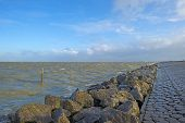 foto of dike  - Basalt stones along a dike in a stormy sea - JPG