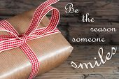 stock photo of proverb  - Gift With Red Ribbon Saying Be The Reason Someone Smiles on Wooden Background - JPG