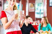 stock photo of diners  - Friends or couple eating fast food and drinking milk shakes on bar in American fast food diner - JPG