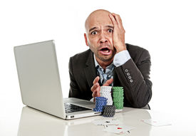 stock photo of spanish money  - desperate addict businessman on computer laptop loosing lots of money betting on internet poker with cards and chips on online gambling addiction isolated on white - JPG