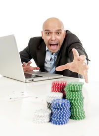 pic of spanish money  - desperate addict businessman on computer laptop loosing lots of money betting on internet poker with cards and chips on online gambling addiction isolated on white - JPG