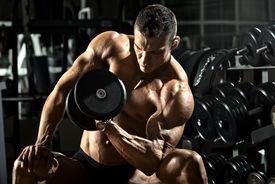pic of bodybuilder  - very power athletic guy bodybuilder execute exercise with dumbbells in dark gym - JPG