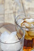 stock photo of coca-cola  - one glass of cola and one empty glass with ice cubes on rustic wooden table - JPG