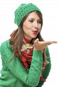 picture of sweethearts  - Romantic pretty young woman in a knitted green winter outfit blowing a kiss across the palm of her hand to her sweetheart or while flirting isolated on white - JPG