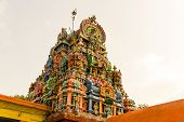 stock photo of shiva  - Magnificent colourful Gopuram of Shiva temple on a blue sky background - JPG