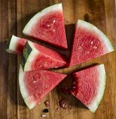 stock photo of watermelon slices  - Sliced juicy watermelon on wooden chopping board in kitchen - JPG