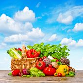 foto of wooden basket  - Fresh vegetables and herbs on wooden background over beautiful blue sky - JPG