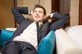 image of daydreaming  - Daydreaming in the hotel. Young handsome businessman sitting in the lobby of luxury hotel and daydreaming with his hands above his head