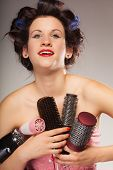 stock photo of hair curlers  - Young woman preparing for date having fun cute girl with curlers styling hair with many accessories comb brush hairdreyer on gray - JPG