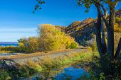 stock photo of bluff  - railroad tracks run between the mississippi river and wooded bluffs in southeastern minnesota autumn - JPG