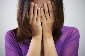 pic of shy woman  - Playful shy woman hiding face laughing timid - JPG