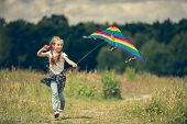 picture of kites  - little cute girl flying a rainbow kite in a meadow on a sunny day - JPG