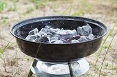 stock photo of charcoal  - Smouldering charcoal in small grill at beach - JPG