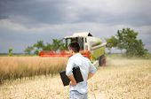 image of combine  - Young businessman with laptop standing in front of combine during harvest - JPG