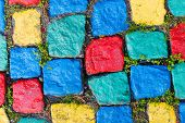 pic of cobblestone  - Old colorful painted granite cobblestone background with grass - JPG