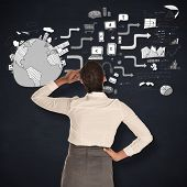 picture of scratching head  - Businesswoman scratching her head against blackboard - JPG