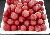 foto of fruit platter  - Top view of frozen currants covered with ice crystals in a white porcelain bowl on a slate platter - JPG